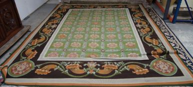 A needlework carpet, with repeat flowerhead green ground enclosed by a pale blue border,