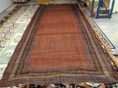 A Saraband long carpet, Persian, the madder field with an allover boteh design,