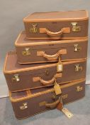 A group of four early 20th century leather bound canvas suitcases,
