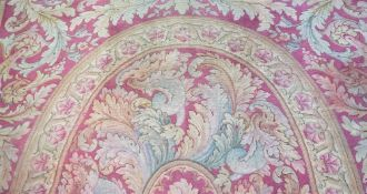 A Savonnerie carpet, French, the red field with a central oval, surrounded by bold leaf sprays,