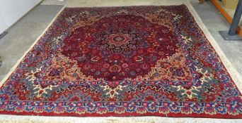 A Mashad carpet, Persian, the dark madder field with a black and madder rosette medallion,