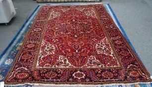 A Heriz carpet, Persian, the madder field with a bold dark indigo medallion, ivory spandrels,
