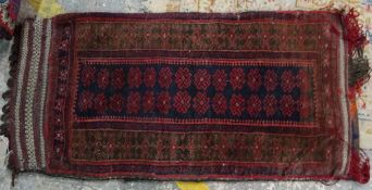 A Beluchistan bag, the indigo field with two columns of madder flowerheads, a brown flower border,