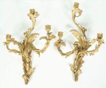 A pair of Louis XVI style gilt bronze three branch wall appliques of foliate rococo design,