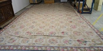 A needlework carpet, the cream ground with a series of flower motifs in a grid design,