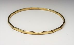 A 9ct gold circular bangle, having faceted decoration, internal diameter 6.5cm, weight 10.5 gms.
