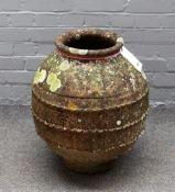 A terracotta oil jar of globular form with wrigglework bands, 45cm diameter x 55cm high.