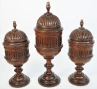 A garniture of three oak vases and covers, late 19th century, each of turned fluted form,