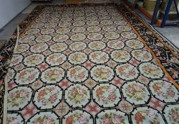 A large needlework carpet, decorated with floral octagons, enclosed by a black bird border, modern,