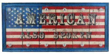 A modern hardwood sign with an American flag decoration 'AMERICAN ALSO SPOKEN',