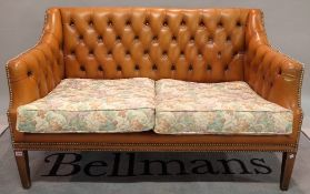 A modern hardwood framed two seater sofa with tan leather buttonback upholstery on tapering square