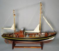 A modern wooden model of a boat on a stand, 49cm long.