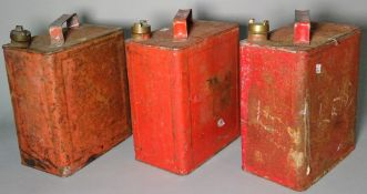 A group of three early 20th century red painted petrol cans, 25cm wide x 28cm high, (3).