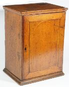 An 18th century inlaid oak hanging spice cupboard, the single door enclosing six drawers,