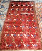 A Khoran rug, the burgundy field rows of pairs of lily flowerheads, a brown chequered border,