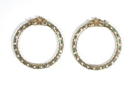 An Asian pair of gold and varicoloured gem-set circular hinged bangles, each mounted with green,