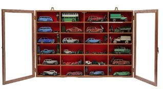 Twenty-four pre-war Dinky die-cast vehicles and related items in a glazed mahogany wall cabinet,
