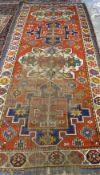 A Kazakh rug, Caucasian, the madder field with two large ivory and two large indigo medallions,