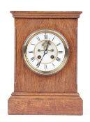 An Edwardian oak cased mantel clock with visible brocot escapement,