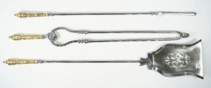 A set of Victorian polished steel fire irons, with brass handles, and a pierced shovel plate, 78cm,