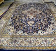 An Indian carpet, the indigo field filled with floral sprays, a central ivory border,