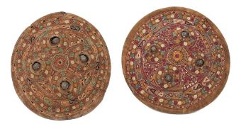 Two Indian Dhal shields, with embroidered covers with a repeated design on a maroon and rust ground,