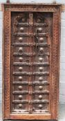 A 19th century Eastern carved hardwood window, with double arch panel doors, 61cm x 119cm high.