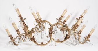 A pair of Louis XVI style gilt metal six branch wall lights, modern, hung with cut glass drops,