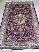 An Indian rug, the madder field with a central ivory medallion,