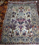 A fine Esfahan rug, Persian, the ivory field with a winged medallion, two flowering trees,