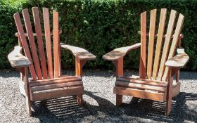 A pair of vintage stained slatted pine loggia armchairs.