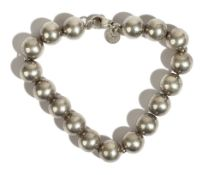 A Tiffany & Co silver bracelet, formed as a row of spherical beads, on a sprung hook shaped clasp,