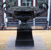 A black painted cast iron twin handle urn, on square stand, 63cm wide x 61cm high.
