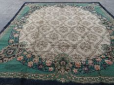 A Donegal carpet, the fan roundel with a trellis, each section centred with a flowerhead,