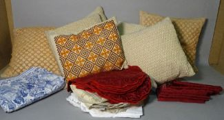 A group of assorted cushions and a bag of fabric and napkins.
