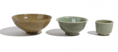 A Chinese celadon bowl, the interior incised with foliate scrolls beneath an olive green glaze,