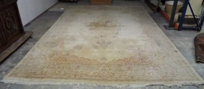 A Kerman carpet, Persian, the plain ivory field with an elongated floral medallion,