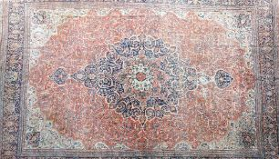 A large antique Kashan carpet, Persian, the madder field with a bold dark indigo,