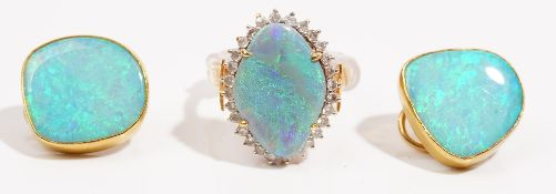 A precious yellow metal opal and diamond-set dress ring The precious opal claw-set to a surround of