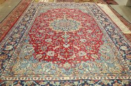 A Kasham carpet, Persian, the madder field with a dark indigo medallion, pale indigo spandrels,