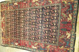 A Tehran rug, Persian, the dark indigo field with rows of botehs; a burgundy border of trees, birds,