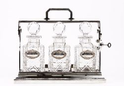 A silver plated tantalus, 20th century, with three cut glass decanters having silver labels,