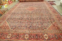 A Hamadan carpet, Persian, the dark indigo field with a bold madder diamond, and spandrels,