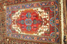 A Hamadan rug, Persian, the ivory held with a large madder medallion,
