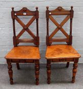 A pair of Gothic Revival oak and walnut hall chairs, with X-frame backs, 46cm wide x 101cm high.