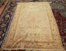 A Hereke silk rug, Turkish, the ivory field with a pale madder shaped medallion,