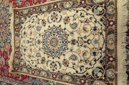 An Esfahan mat, Persian, the ivory field with a central indigo medallion,