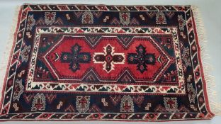 A Southern Anatolian rug, modern, with three star motifs, on a red ground, 182 x 124cm.