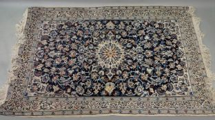 A modern Iranian rug, with a central medallion surrounded by flowering branches, on a blue ground,
