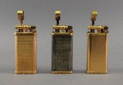 Three Alfred Dunhill lighters, of oval s